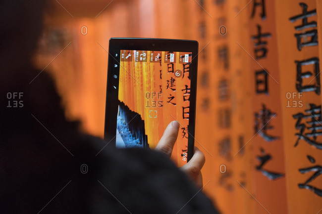 Woman taking a photograph of the Torii Gates, Fushimi, Inari Shrine, Kyoto, Japan