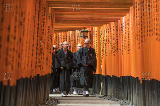 Kyoto, Japan - November 17, 2015: Shinto monks walking through Torii Gates, Fushimi, Inari Shrine, Kyoto, Japan