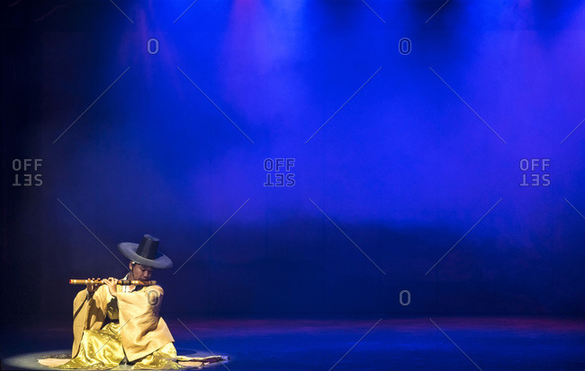 Seoul, South Korea - November 26, 2015: Musician in traditional dress playing Korean flute on stage in Seoul, South Korea
