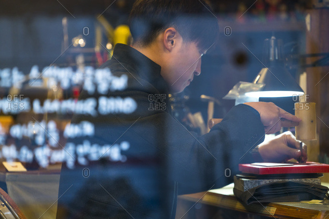 Seoul, South Korea - November 28, 2015: View through a shop window of a man working on leather goods in Bukchon, Seoul, South Korea