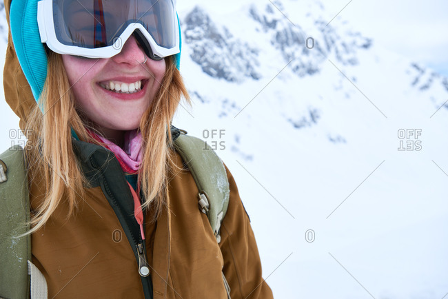 Portrait of a woman wearing ski goggles in mountains