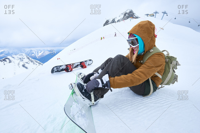 Woman strapping on her snowboard