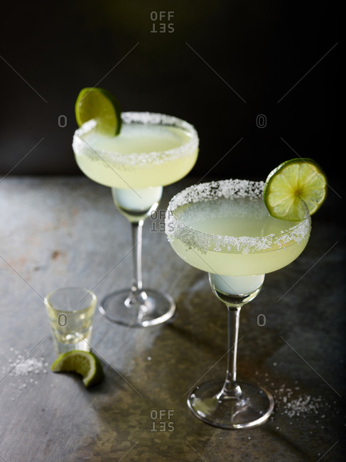Two margaritas with an empty shot glass