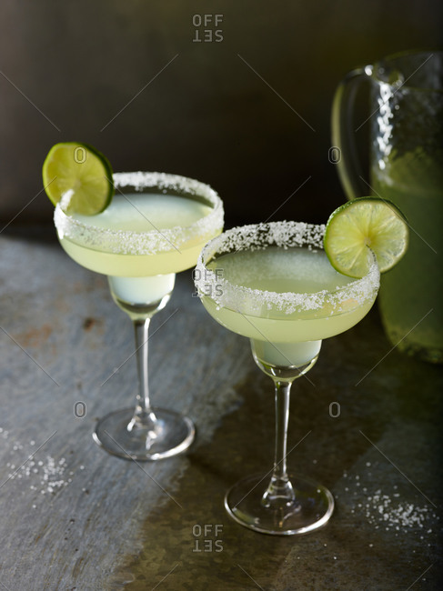 Two margaritas garnished with salt and limes