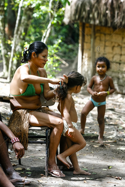 Porto Seguro, Brazil - March 19, 2010: Pataxo mother tying back her daughter's hair at the Reserva Indigena da Jaqueira