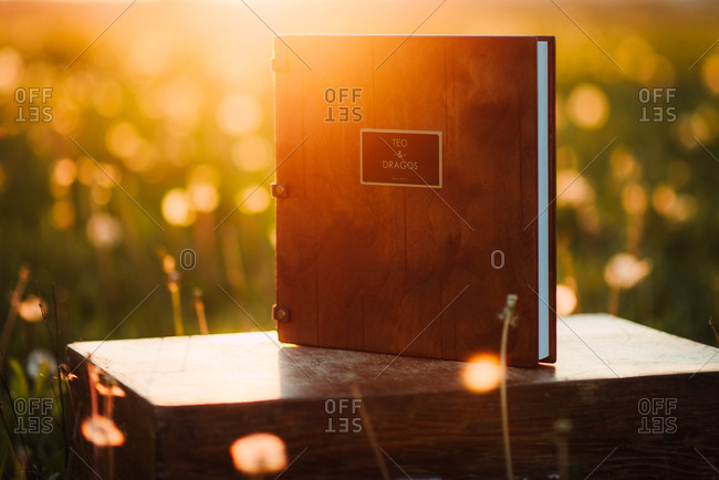 Couple's album resting on wooden box in field at sunset