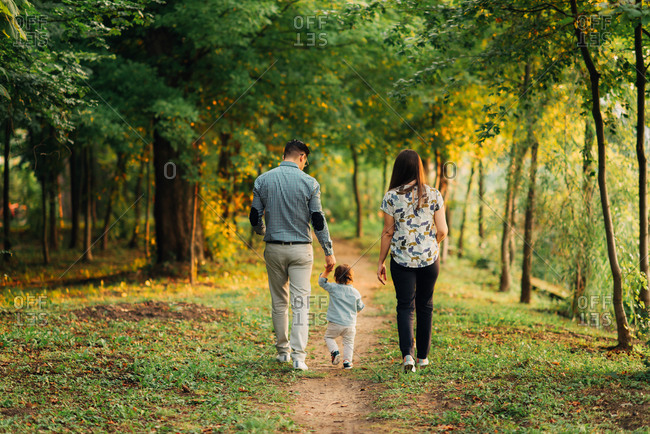 Couple walking with baby on path in woods at dusk