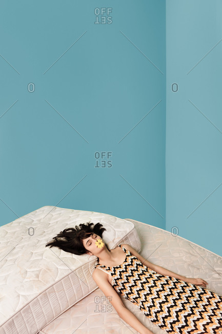Young woman on a bed in a blue room