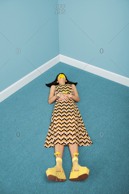 Young woman lying on the floor in a blue room