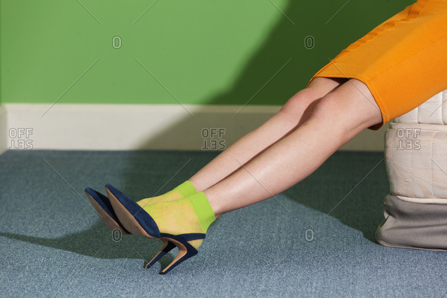 Legs of a woman wearing high heels and green socks