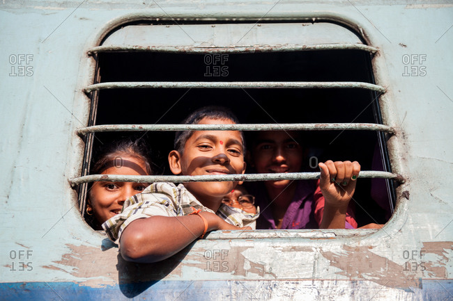 December 26, 2015: Smiling children looking through the window of a train car