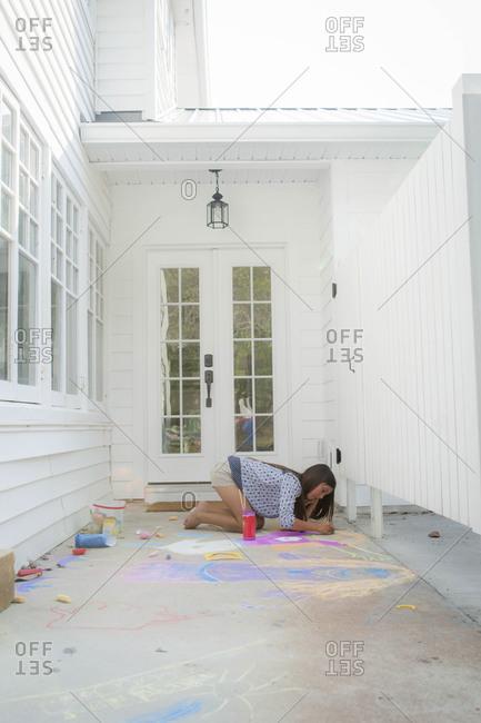 Girl drawing on a sidewalk with chalk