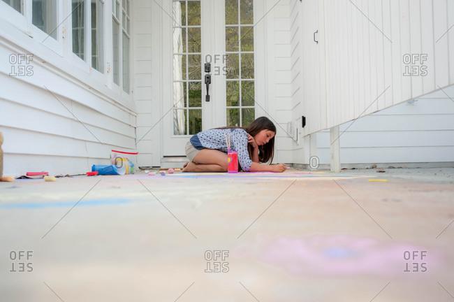 Girl drawing with sidewalk chalk