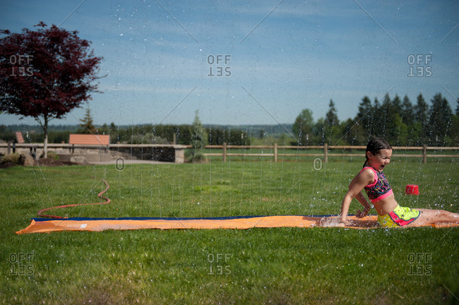 Girl playing on a water slide on her lawn