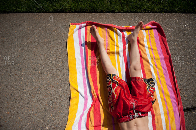 Overhead view of a boy lying down on a beach towel on the sidewalk