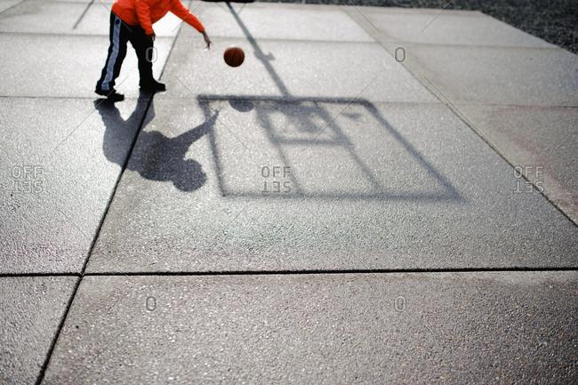 Boy playing basketball outside