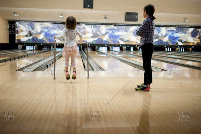 Two girls bowling at a bowling alley