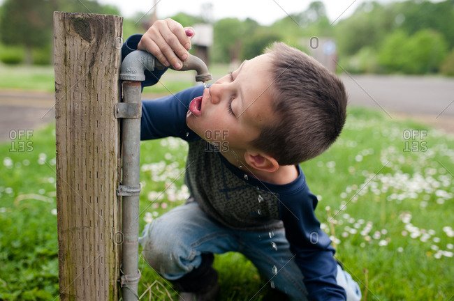 Boy drinking from an outdoor spigot