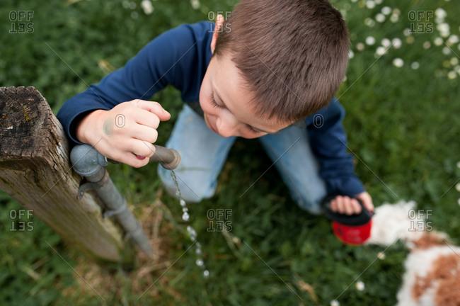 Boy drinking from an outdoor spigot