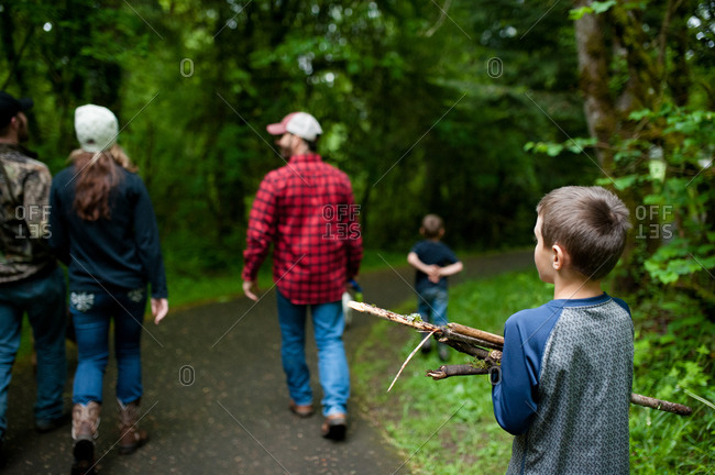 Boy holding a bundle of sticks behind a group of adults on a wooded path