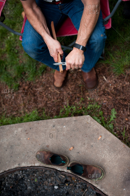 Overhead view of a man whittling near a fire pit