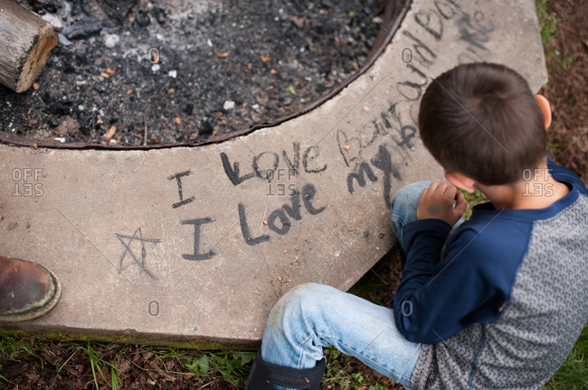 Overhead view of a boy using soot to write on the side of a concrete fire pit