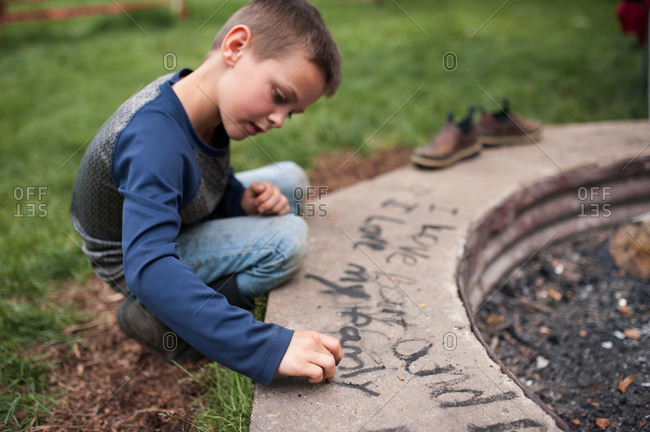 Boy using soot to write on the side of a concrete fire pit