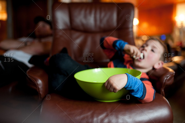 Boy reclining in a chair while eating a bowl of popcorn