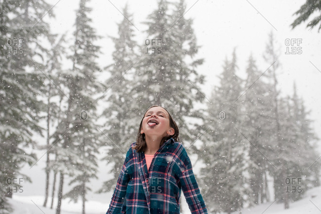 Girl standing outside catching snowflakes on her tongue