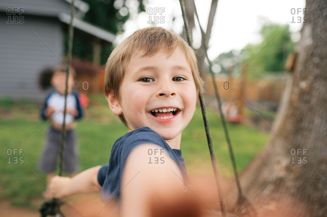 Close-up of a boy on a swing in his backyard