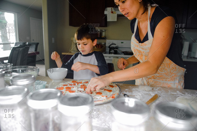 Boy helping his mother make pizza