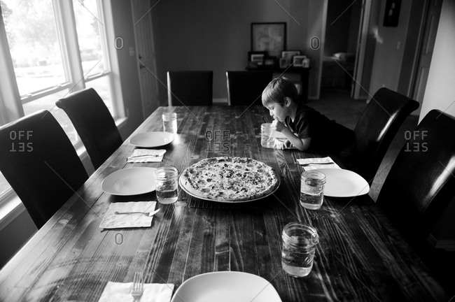 Boy drinking water at a dining room table set with a pizza, plates, and glasses