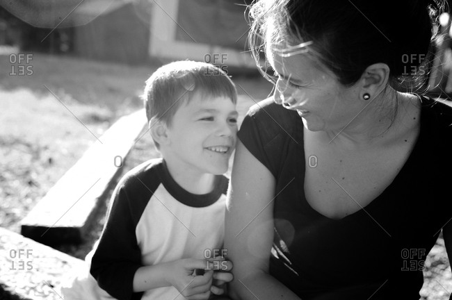 Boy sitting outside with his mother