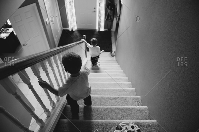 Two boys walking down stairs in their house