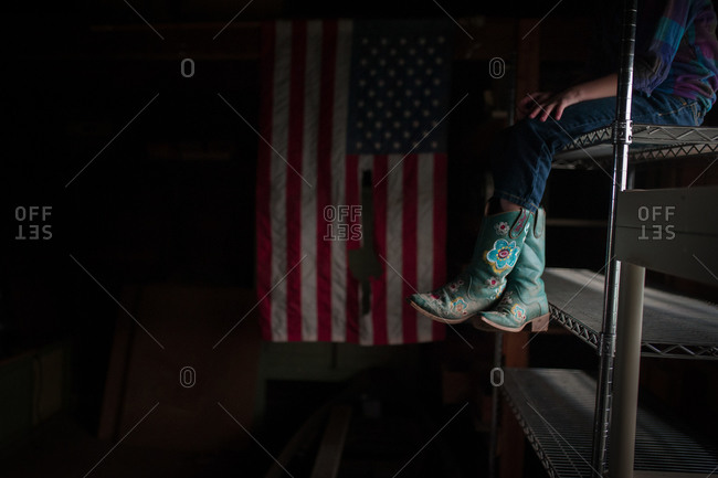 Girl wearing cowboy boots sitting in a dimly lit room next to an American flag