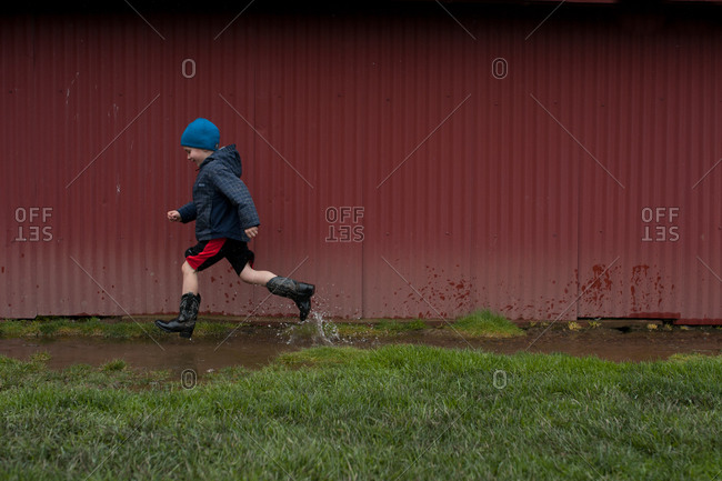 Boy running through puddles along the side of a red barn