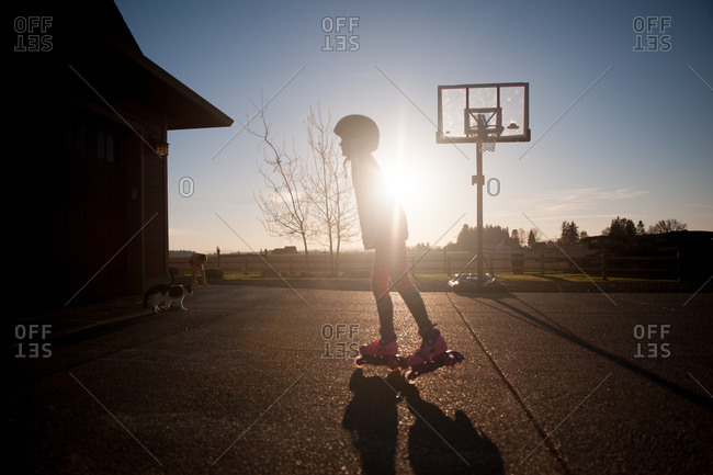 Silhouette of a child rollerblading in a driveway