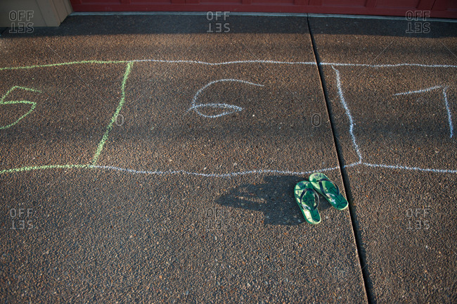 A pair of flip flops sitting on the pavement next to a hopscotch outline
