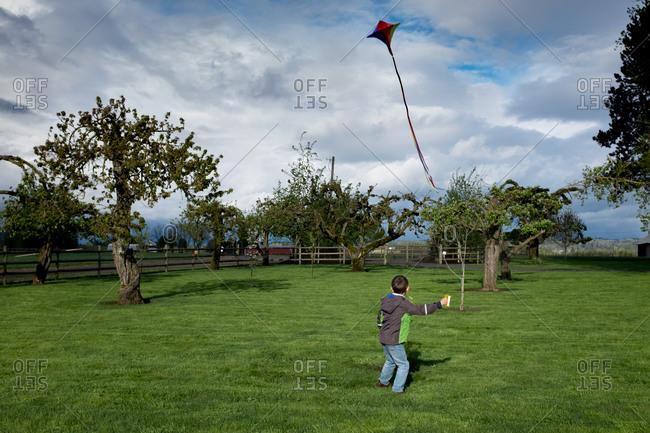Boy flying a rainbow striped kite