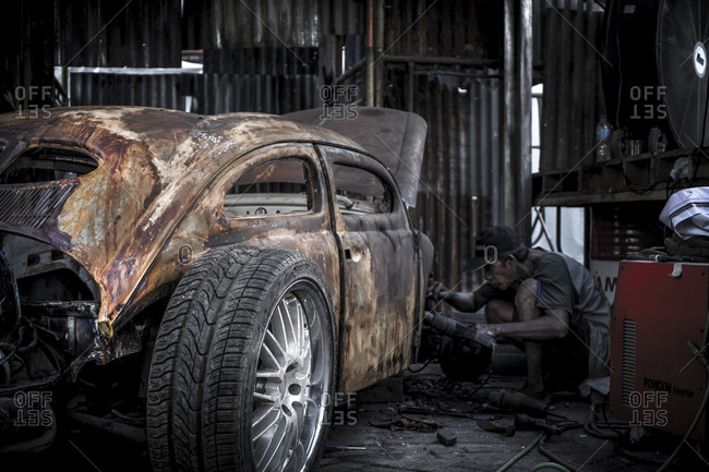 Jakarta, Indonesia - April 12, 2016: Man working on an old car