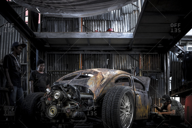 Jakarta, Indonesia - April 12, 2016: Two men looking at rusty car as another man changes a tire