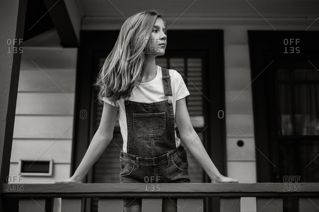 Girl leaning on porch rails waiting