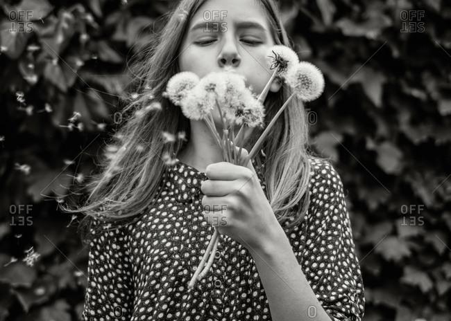 Girl blowing dandelion seeds
