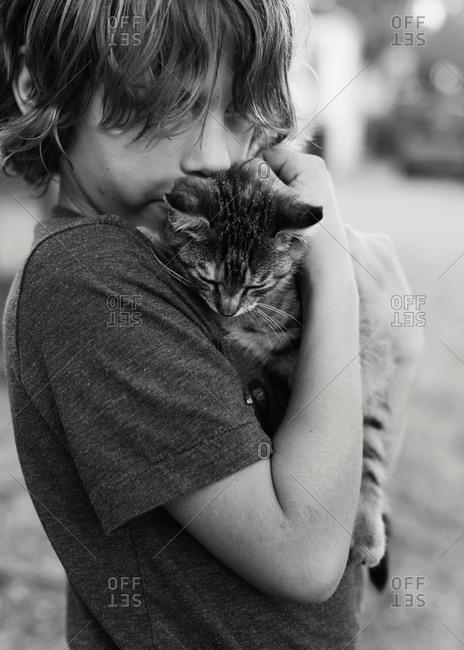 A boy embracing a kitten