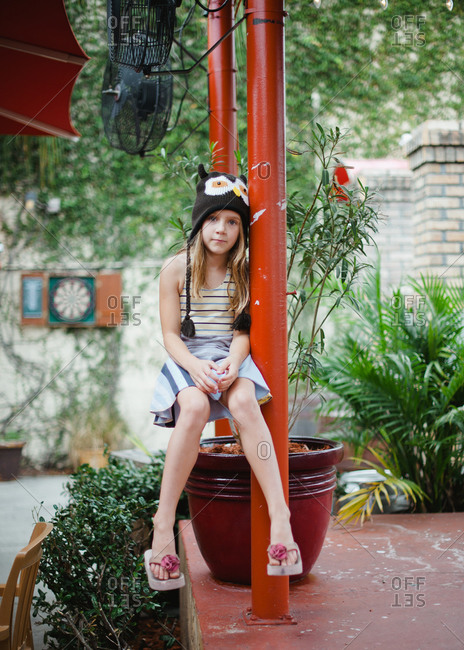 Girl wearing an owl hat sitting on the patio