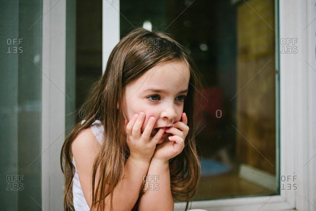 Preschool age girl sitting by a patio door