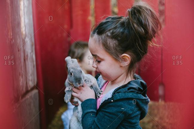 Girl holding a short-haired rabbit