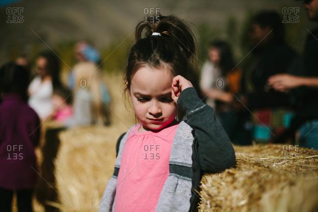 Little girl standing in hay