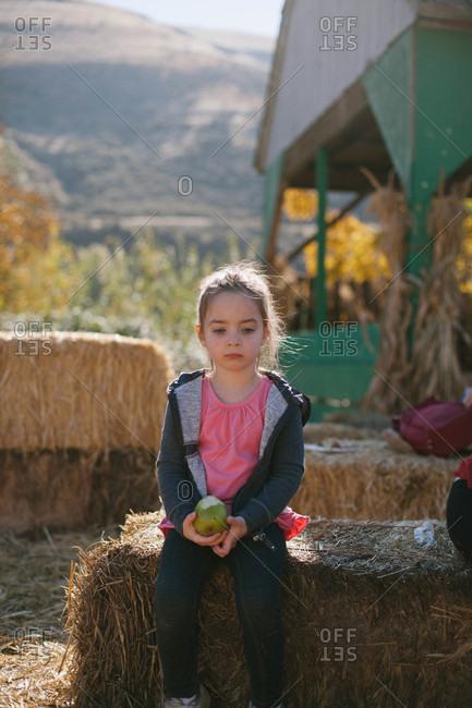 Girl eating an apple sitting on hay bale