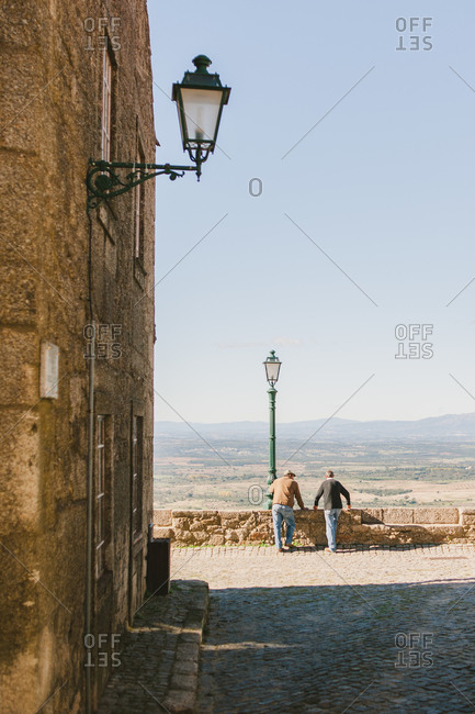 Men looking over ledge at the countryside in Monsanto, Portugal
